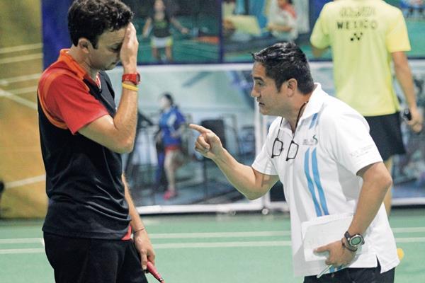 Kevin Cordón conversa con su entrenador José María Solis en una de las prácticas en la Federación de Bádmintos. (Foto Prensa Libre: HemerotecaPL)