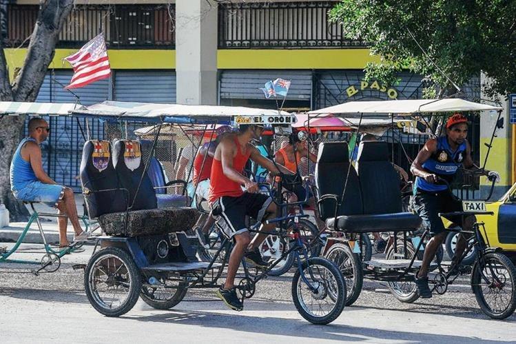 Un bicitaxi está adornado con una bandera de EE.UU. en una de las calles  en La Habana, Cuba. (Foto Prensa Libre:AFP).