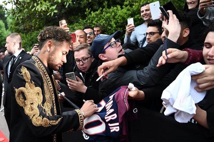 Neymar cuando ingresa y firma autógrafos a los aficionados previo a la gala del futbol francés. (Foto Prensa Libre: AFP)