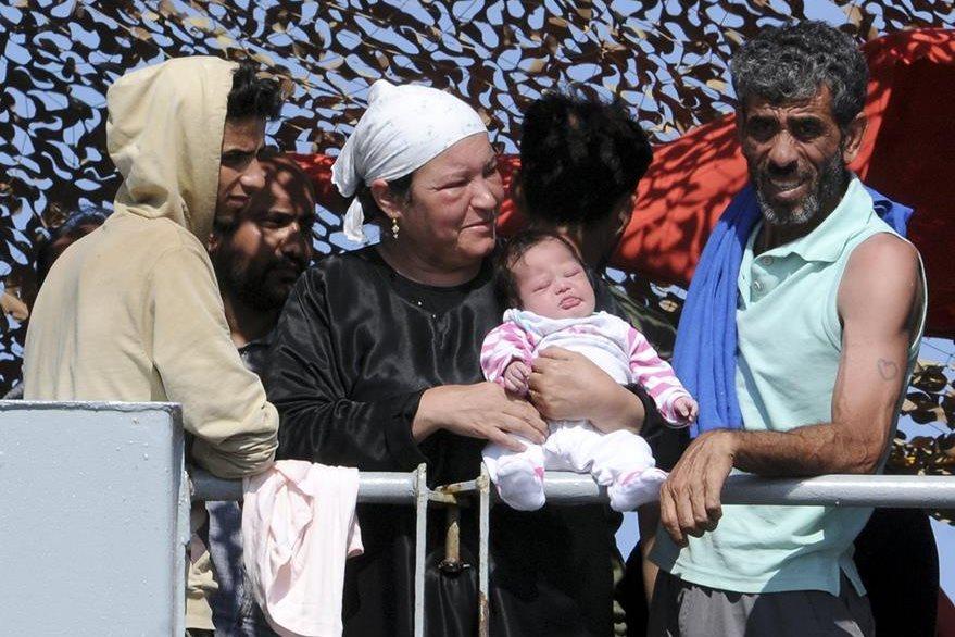 Una familia de Inmigrantes con un bebé, esperan desembarcar en el puerto de Palermo, Italia. (Foto Prensa Libre: AP).