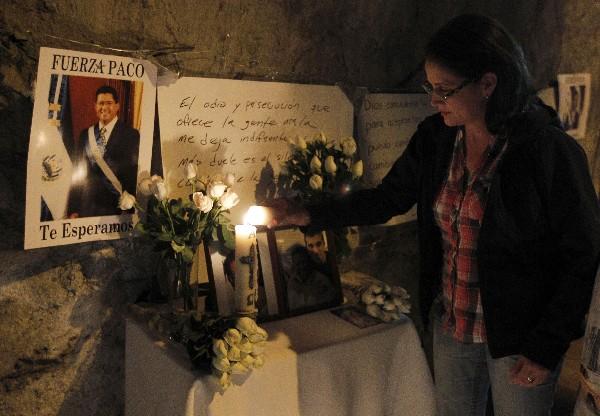 Una salvadoreña enciende una vela en memoria de Francisco Flores.