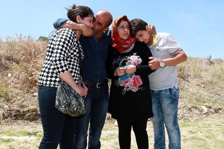 Rashid Jaqali y su familia, se abrazan al concluir la travesía en Italia, lamentan la muerte de uno de sus integrantes Mohamad. (Foto Prensa Libre: AP).