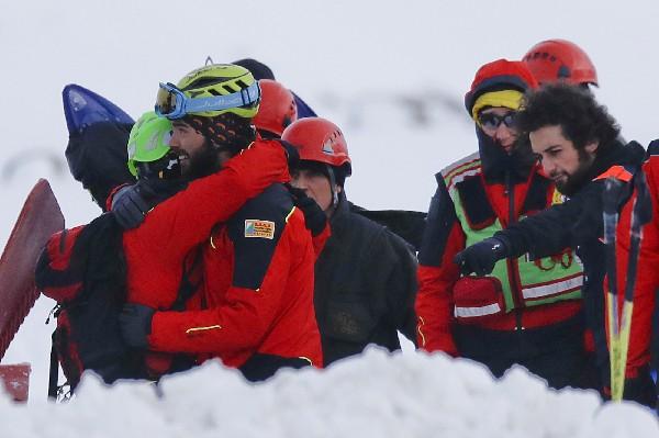 Rescatistas se abrazan en el sitio donde un helicóptero se estrelló en el Campo Felice, Italia. (AFP).