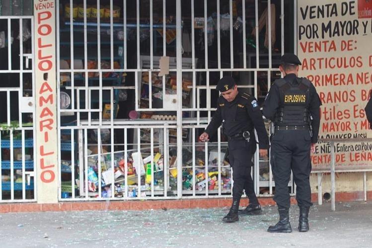 Policías observan indicios en la escena de la explosión. (Foto Prensa Libre: Estuardo Paredes)