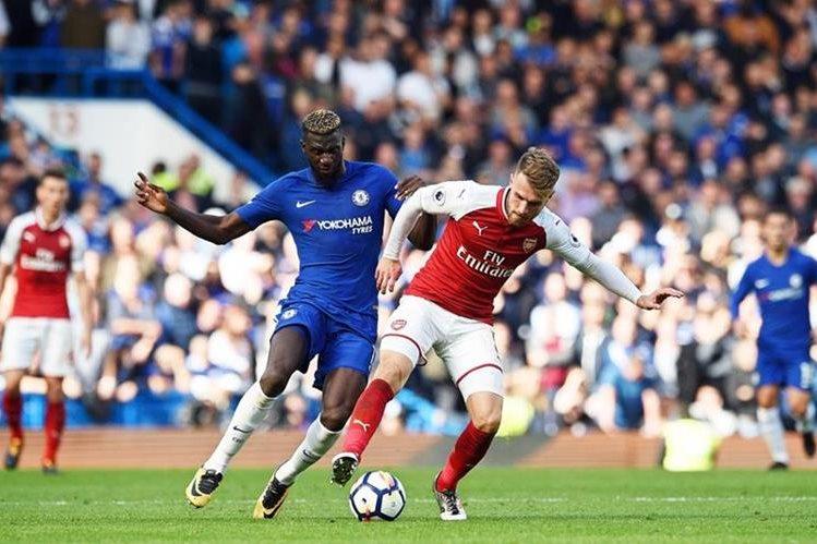 Tiemoue Bakayoko trata de detener a Aaron Ramsey en el juego entre el Chelsea y el Arsenal. (Foto Prensa Libre: EFE)