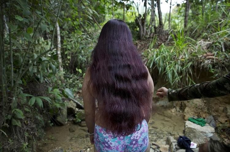 In this Jan. 5, 2016 photo, Marcela, a rebel soldier of the 36th Front of the Revolutionary Armed Forces of Colombia, or FARC, stands at the edge of a brook where she is preparing to bathe, near the guerrilla