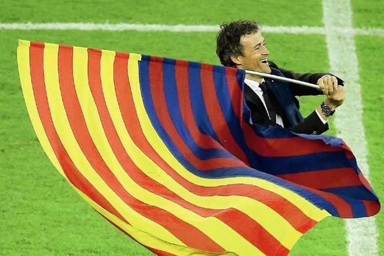 El técnico Luis Enrique ondea la bandera catalana junto a la del FC Barcelona en la celebración del triunfo en la Champions League. (Foto Prensa Libre: AFP)