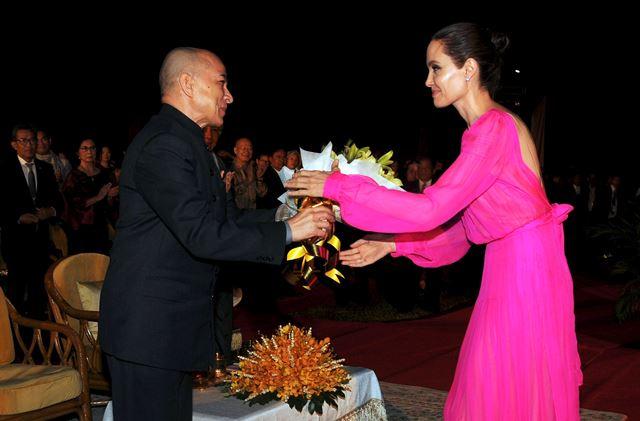 El rey de Camboya, Norodom Sihamoni, entrega flores a Angelina Jolie en una ceremonia, el sábado. (Foto Prensa Libre: EFE).