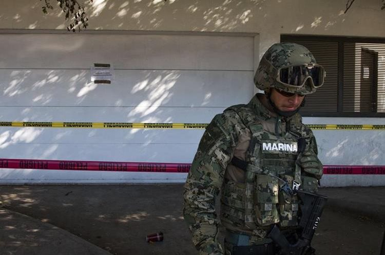 "A marine stands guard outside the house where five gang suspects were killed in the military operation which resulted in the recapture of Joaquin ""El Chapo"" Guzman on January 8 in the city of Los Mochis, Sinaloa State, Mexico, on January 10, 2016. Mexican marines recaptured fugitive drug kingpin Joaquin ""El Chapo"" Guzman on January 8 in the northwest of the country, six months after his spectacular prison break embarrassed authorities. AFP PHOTO/HECTOR GUERRERO"