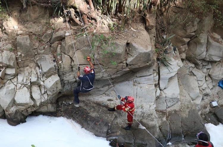 Dos bomberos sacan el cadáver del barranco donde cayó. (Foto Prensa Libre: CBM)