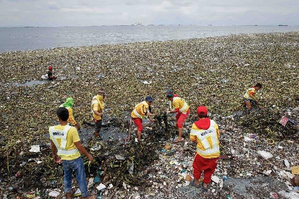 Equipos de limpieza trabajan para limpiar la bahía de Manila afectada por el tifón Nida.