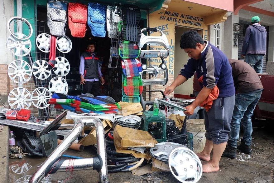Comerciante de la zona 2 de Xela limpian su negocio que fue inundado por correntadas ocasionadas por la fuerte lluvia del lunes último. (Foto Prensa Libre: Carlos Ventura)