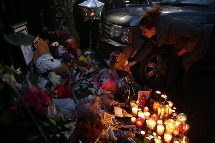 Fanáticos entregan homenajes florales en memoria del cantante George Michael. (Foto Prensa Libre: AFP)