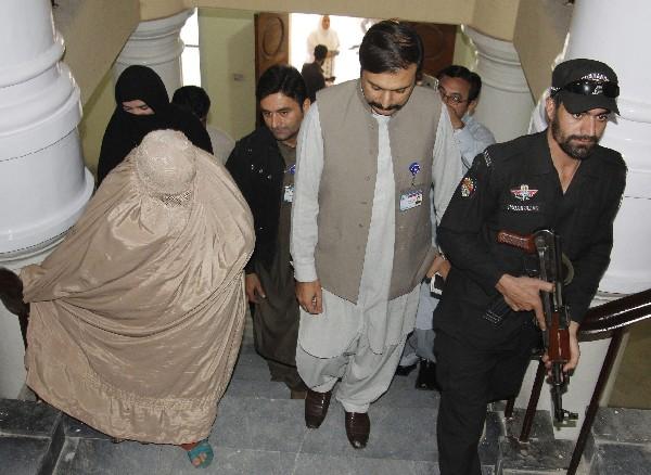 Sharbat Gula, (i) abandona el hospital antes de acudir al juzgado en Peshawar. (EFE).