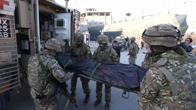 Soldados británicos cargan el cuerpo de una de las víctimas del ataque. (Foto Prensa Libre: AP)