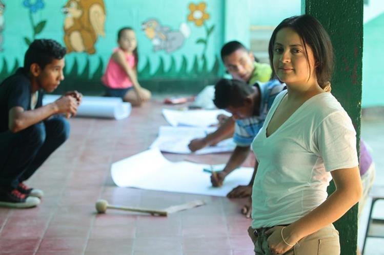 Jazmín Carrillo junto con los niños de la escuela que son beneficiados con la red de amigos que esta migrante formó en Estados Unidos Foto: Álvaro Interiano