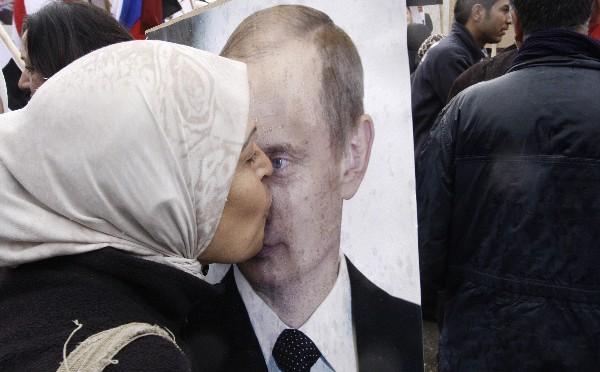 una siria besa un cartel del presidente ruso, Vladimir Putin, durante una protesta en Damasco, Siria.