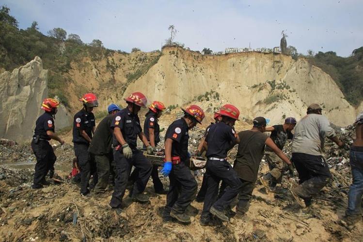 Bomberos Municipales realizan el rescate de una persona que quedó soterrada por el alud. (Foto Prensa Libre: Edwin Bercián)