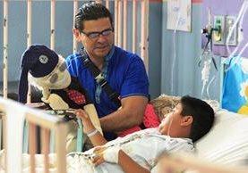 El abuelo Lalito conversa con Julio García, de 10 años, en la Pediatría del hospital mientras Luis Fernando Reyes Cáceres da vida con su arte al personaje. (Foto Prensa Libre: Carlos Hernández)