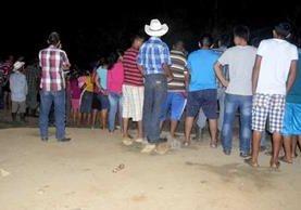 Curiosos permanecen en el lugar del ataque, en Morales, Izabal. (Foto Prensa Libre).