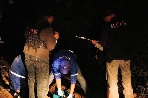 Investigadores de  la PNC y fiscales del MP recogen evidencias en el km 36 de la ruta a Santiago Sacatepéquez, Sacatepéquez, donde un joven murió a balazos. (Foto Prensa Libre: Renato Melgar)
