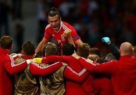 Gareth Bale festeja con sus compañeros, después de una de las anotaciones de Gales. (Foto Prensa Libre: EFE)