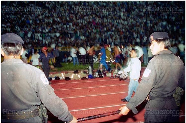 Bomberos Municipales y Voluntarios con la ayuda de particulares colocan en la pista de atletismo los cadáveres de las personas fallecidas en el Estadio Nacional Mateo Flores a causa de una avalancha humana en el Graderío General Sur. 16/10/1996 (Foto: Hemeroteca PL)