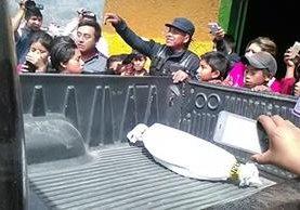Curiosos permanecen junto a patrulla de la PNC que traslada feto localizado en Nebaj. (Foto Prensa Libre: Óscar Figueroa).