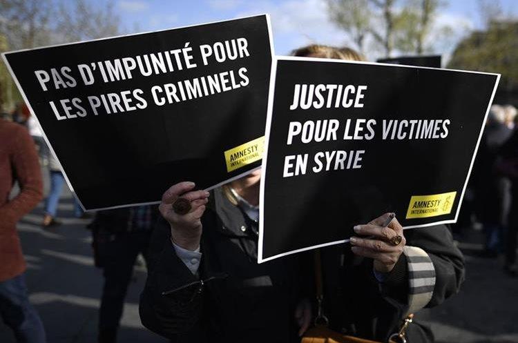Un grupo de manifestantes en París, Francia, exige justicia por las víctimas de ataques con armas químicas.