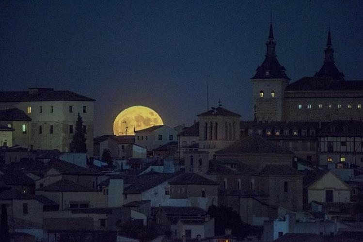 La superluna se asoma tras un vecindario en Toledo, España. (Foto Prensa Libre: EFE).