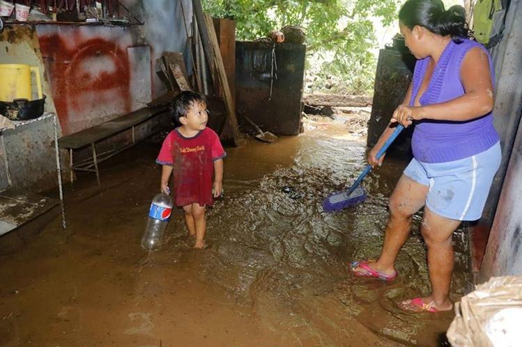 Una mujer saca el agua que se quedó estancada en su vivienda en San Martín Zapotitlán, Retalhuleu.(Foto Prensa Libre: Rolando Miranda)