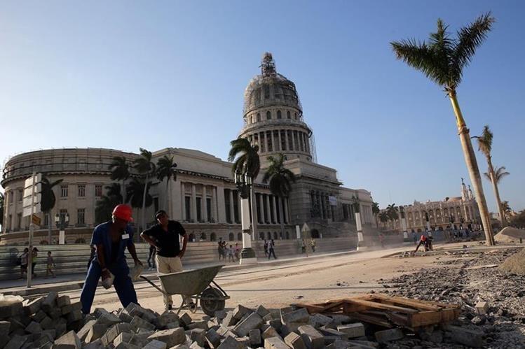 Cuadrillas de obreros sobresalen por estos días entre un número cada vez mayor de turistas. (Foto Prensa Libre: EFE).