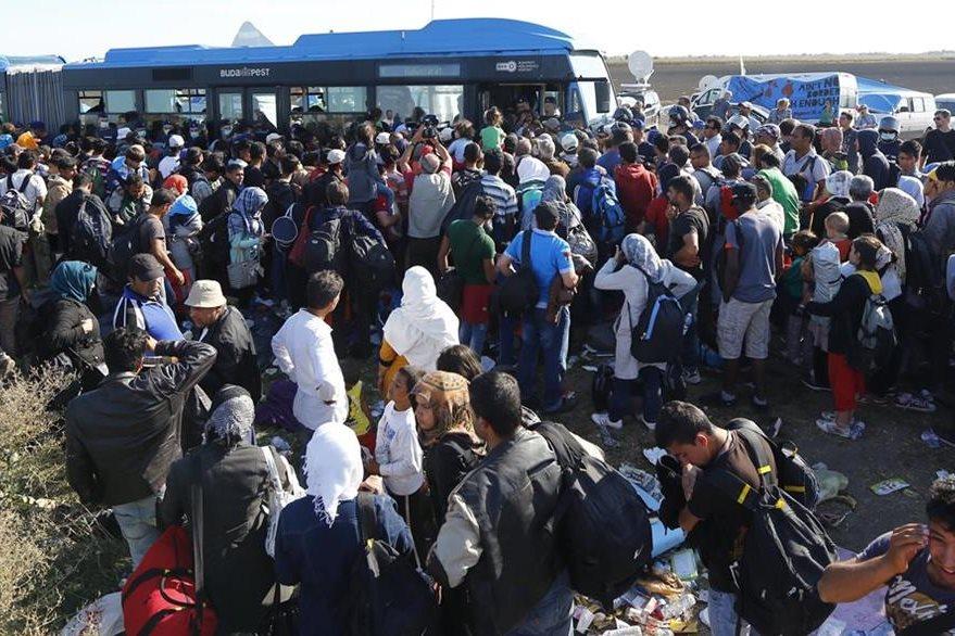 La Policía húngara custodia el traslado de inmigrante sirios hacia los centros de identificación. (Foto Prensa Libre: AP).