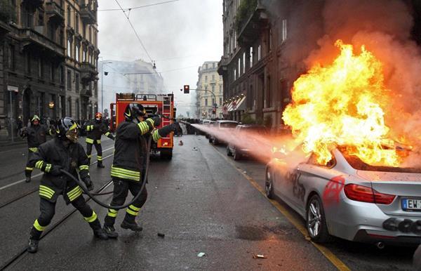Bomberos tratan de apagar un vehículo en llamas durante las protestas en Milán. (Foto Prensa Libre: EFE).