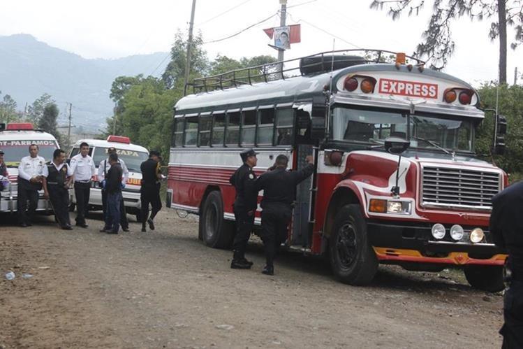 Agentes de la PNC resguardan evidencias dentro de autobús en el que murieron dos hombres, en Chimaltenango. (Foto Prensa Libre: Víctor Chamalé)
