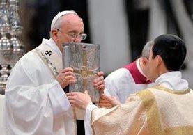 El papa Francisco besa el evangeliario mientras oficia la Misa Crismal en la basílica de San Pedro en el Vaticano este Jueves Santo. (Foto Prensa Libre: EFE).