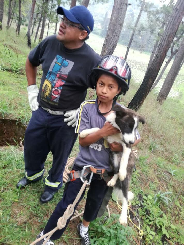 Con ayuda de socorristas, el niño Juan Ajuchán rescató a su perro Boby, en Chimaltenango. (Foto Prensa Libre: Víctor Chamalé)