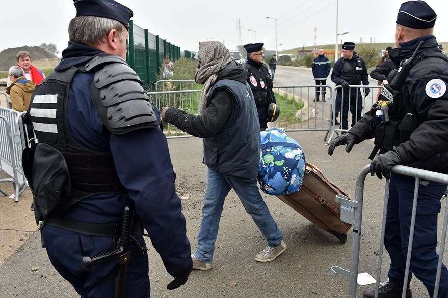 Policías franceses observan a los inmigrantes abandonar el campamento. (Foto Prensa Libre: AFP).