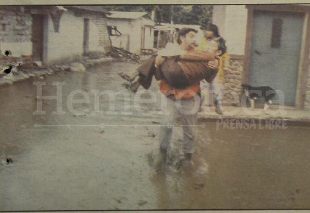 El mayor de bomberos, Victor Quiroz, delegado del CRN en Pochuta carga en sus brazos a un anciano que quedó atrapado en la correntada de lodo en Pochuta. (Foto: Hemeroteca PL)