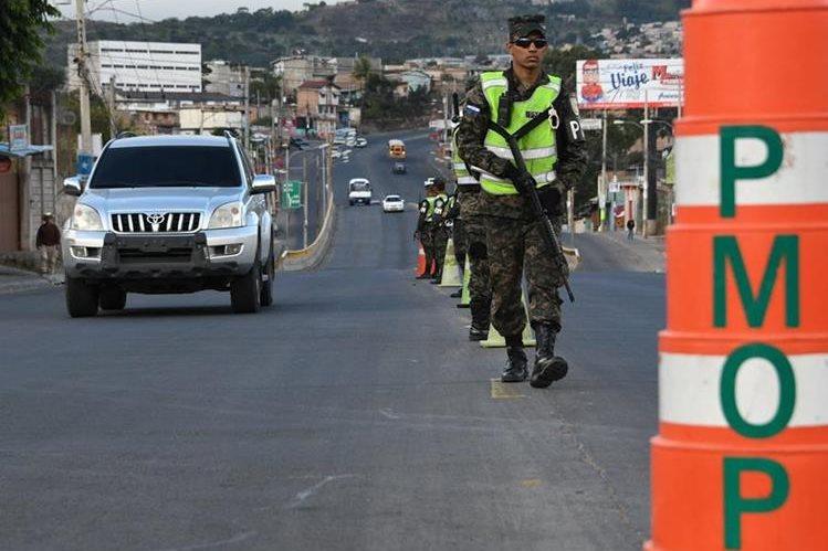 Militares hondureños hacen guardia en Tegucigalpa, durante el estado de emergencia y un toque de queda de 10 días impuesto por el gobierno para detener las manifestaciones. (Foto Prensa Libre: EFP)