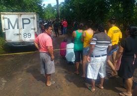 Curiosos observan en el camino de terracería donde fueron hallados los cuerpos de una mujer de 30 años aproximadamente y su bebé, de 2. (Foto Prensa Libre: Rolando Miranda)