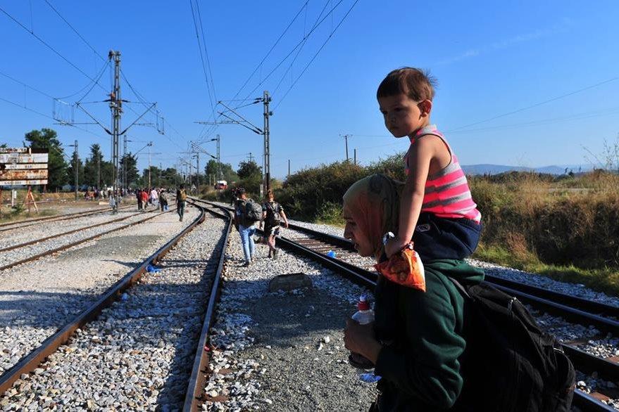 Una mujer carga en hombros a su hijo en un área cercana a la frontera entre Grecia y Macedonia. La inmigrante espera abordar un tren que la lleve a Europa Occidental. (Foto Prensa Libre: AFP).