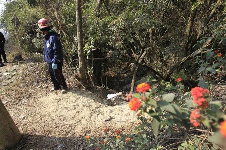 Un bombero observa el cadáver de un hombre, en el km 29 de la ruta de Santa Lucía Milpas Altas, Sacatepéquez, a Bárcenas, Villa Nueva. (Foto Prensa Libre: Carlos Hernández Ovalle)