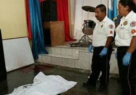 El cadáver de un hombre atacado con arma cortante es resguardado por socorristas en Poptún, Petén. (Foto Prensa Libre: Rigoberto Escobar)