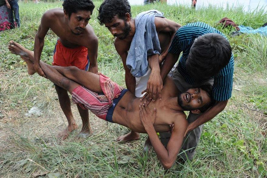 Unos hombres tratan de ayudar a un compañero enfermo que desembarcó en las costas tailandesas. (Foto Prensa Libre: AFP).