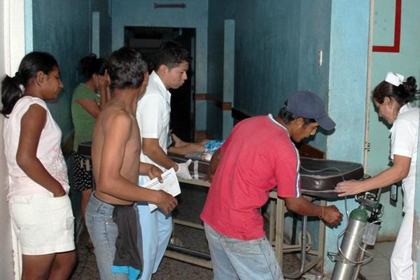 <p>Familiares trasladan a un menor que resultó con un balazo en la cara, a un centro asistencial para ser atendido. (Foto Prensa Libre: Alexander Coyoy)<br></p>