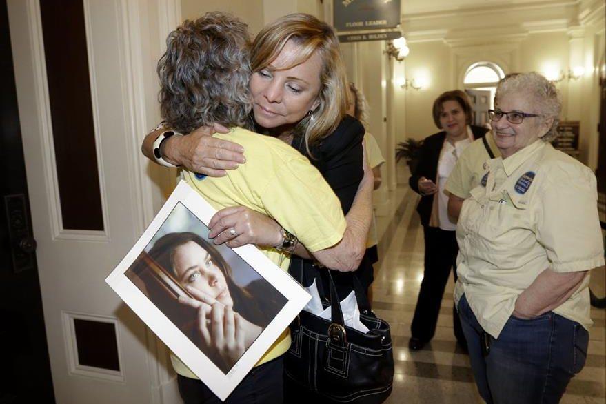 Activistas a favor de la eutanasia se abrazan tras conocer la nueva disposición. (Foto Prensa Libre: AP).