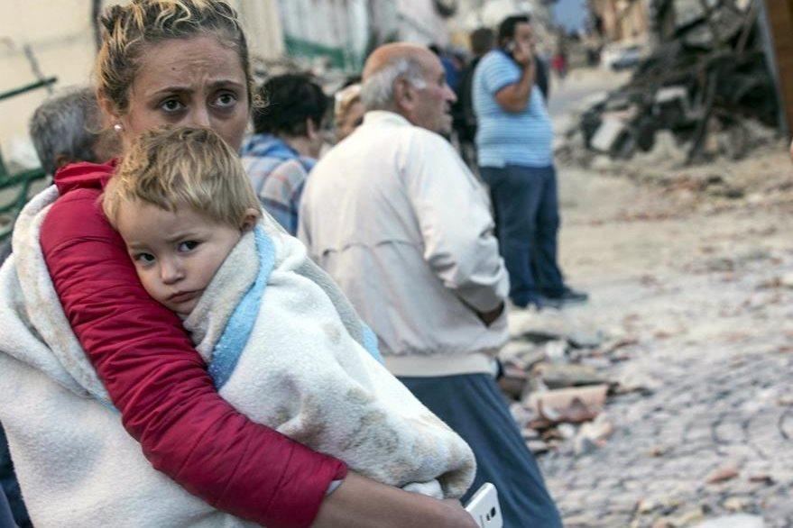 Una mujer abraza a su hija mientras espera ayuda en Amatrice. (Foto Prensa Libre: AP).