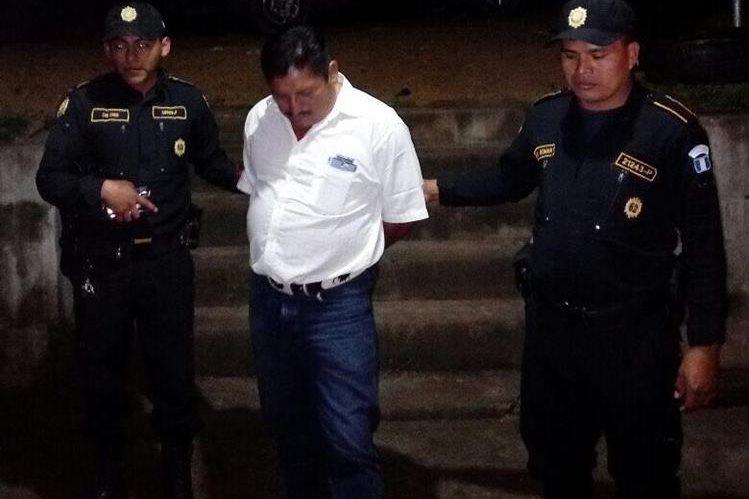 Dos agentes de la Policía Nacional Civil custodian hacia el juzgado a Joel Coy Caal por disparar al aire en el casco urbano de Sayaxché. (Foto Prensa Libre: Rigoberto Escobar)
