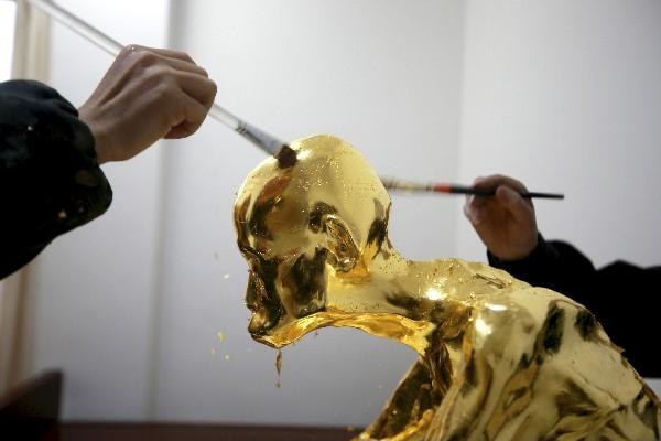 Un experto aplica hojas de oro sobre el cuerpo momificado de Fu Hou. (AP)